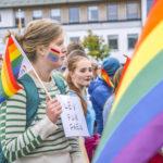 """Folk i paraden med regnbueflagg. kvinne holder """"lev for faen""""-plakat"""