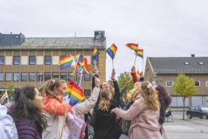 Mange folk hopper med regnbueflagg