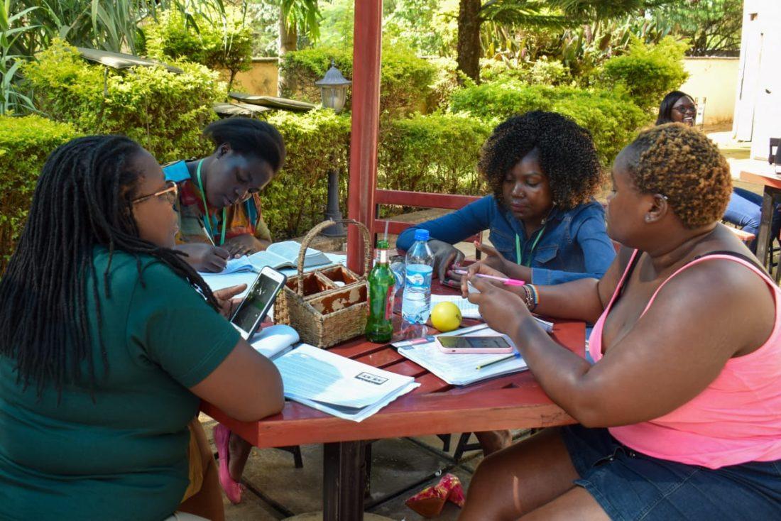 Fire kvinner sitter rundt et bord utendørs
