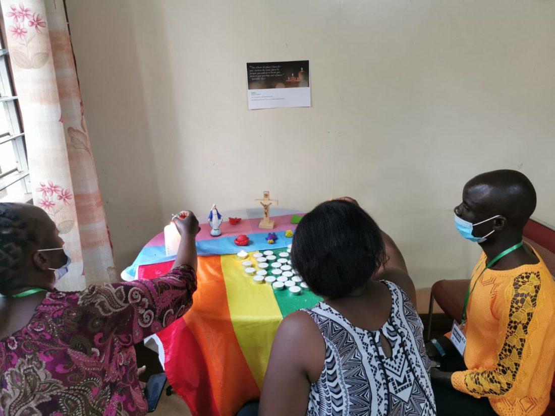Tre folk sitter rundt bord dekorert med regnbueflagg