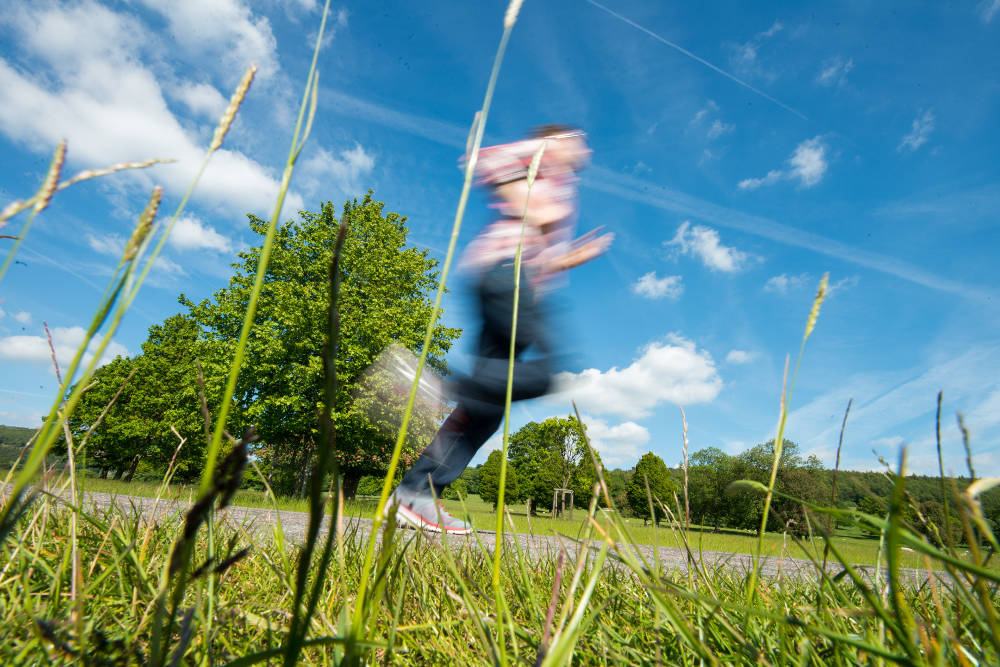 Man Jogging Through Field With Motion Blur