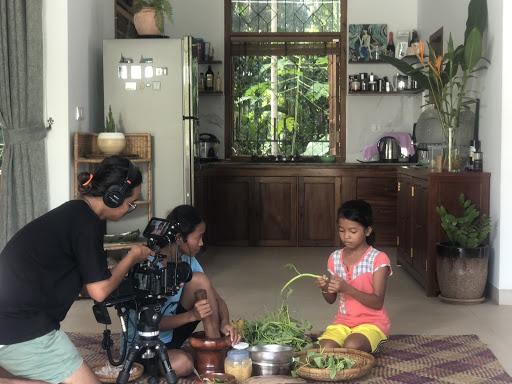 Jente plukker blader fra en urt, mor ser på. En kameramann filmer dem.