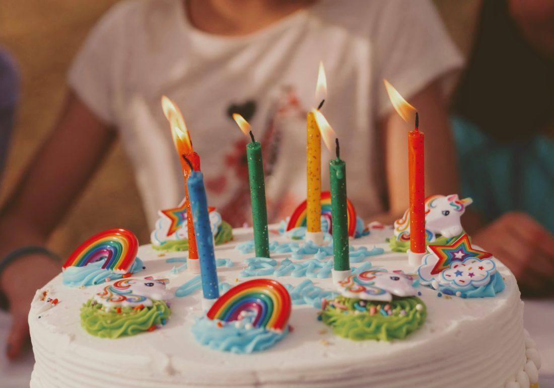 Barn med kake med regnbue-pynt