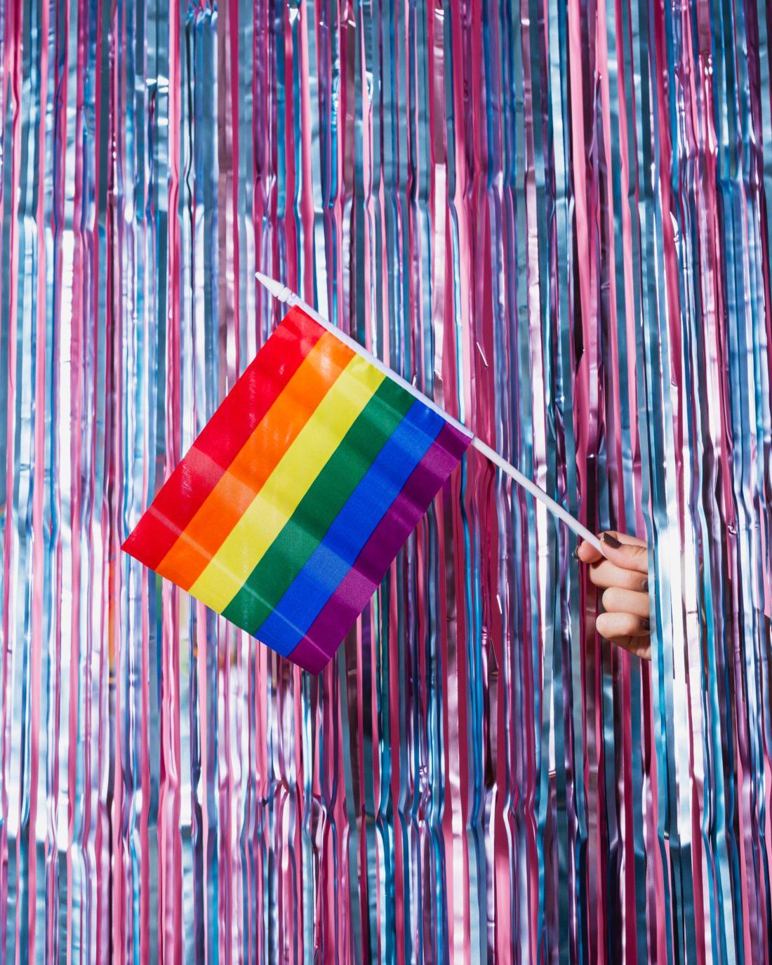Regnbueflagg stikker ut gjennom en glittervegg i bi-flagg-fargene